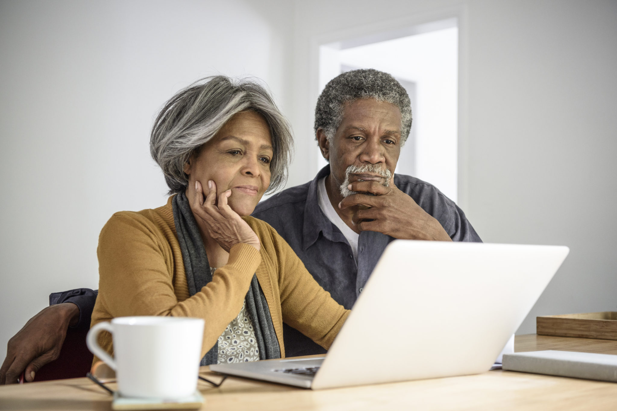 Senior African American couple using laptop, contemplating