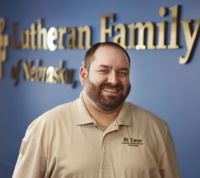Adam Armstrong in front of Lutheran Family Services sign