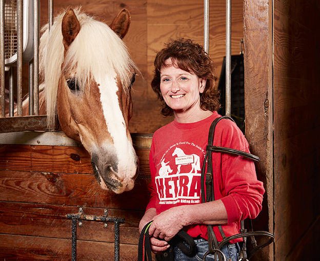 Diane Bemis with a horse in stable