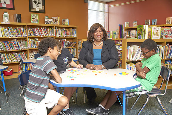 Vanita Jarmon at school desk with students