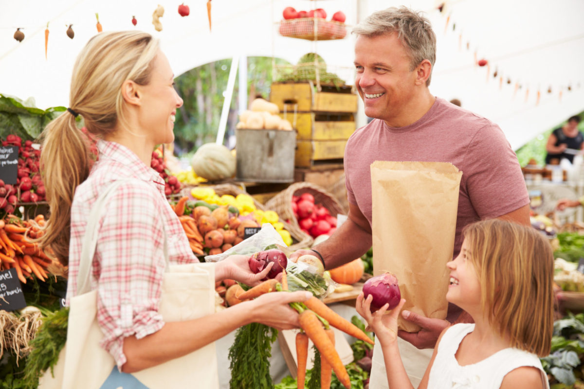Family Buying Fresh Vegetables At Farmers Market Stall, Smiling