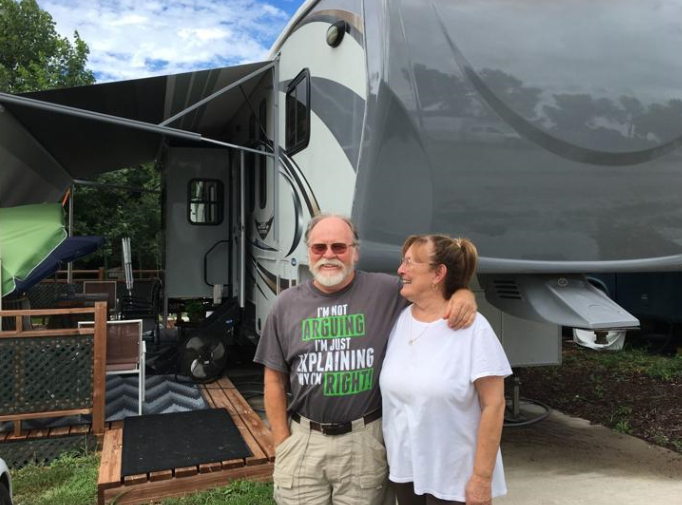Retirees in front of their camper