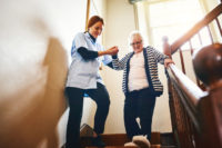 Elderly woman getting help down the stairs