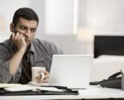 Man unsure looking at laptop