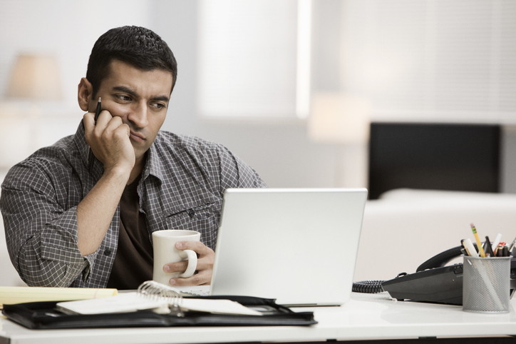 Man unsure looking at laptop