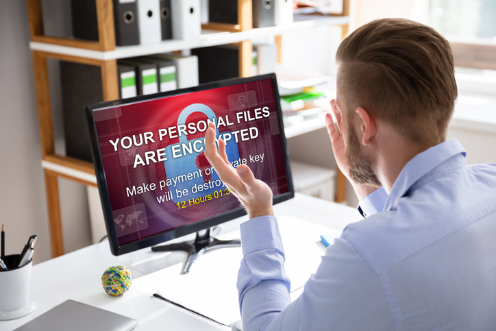 Man looking at computer with ransomware