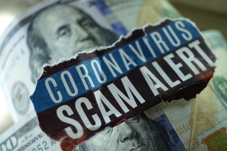 Photo with Coronavirus scam alert written across $100 bills